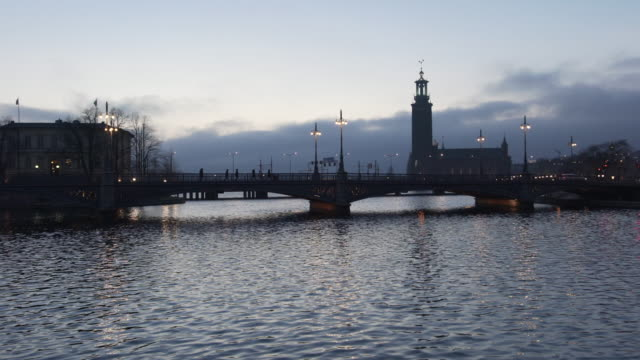 vasabron bridge and the city hall, stockholm, evening - スウェーデン点の映像素材/bロール