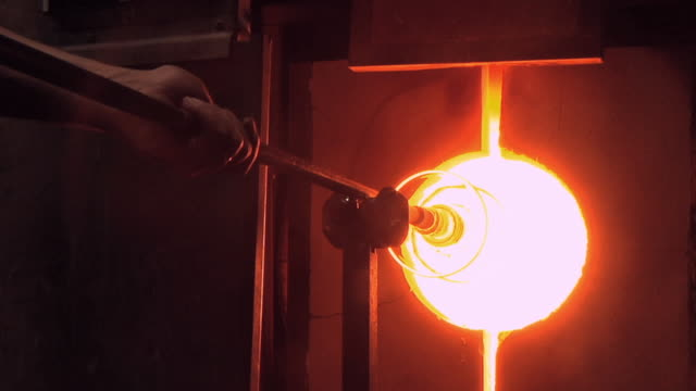 CU Vase on iron torch being placed in 2,300 degree reheating oven at glass blowing factory / Windsor, Vermont, USA