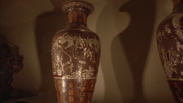 Vases cast shadows on a wall.