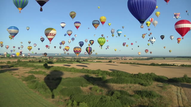 aerial ws vast array of vibrant colored hot air balloons taking off / alsace - lorraine, france - large group of objects stock videos & royalty-free footage