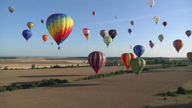 aerial ws vast array of vibrant colored hot air balloons taking off / alsace - lorraine, france - hot air balloon stock videos & royalty-free footage