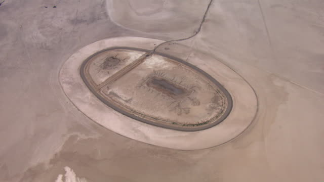 a vast, dry lake bed surrounds an abandoned racetrack in ivanpah valley, california. - lake bed stock videos & royalty-free footage
