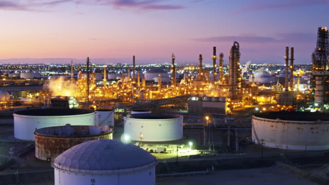 vast oil refinery lit up after sunset - drone shot - industria petrolifera video stock e b–roll