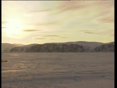 vast snow covered land and mountain range pan left to inuit man leaning over seal breathing hole in ice as sun sets - inuit bildbanksvideor och videomaterial från bakom kulisserna