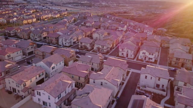 vast suburban development at golden hour - aerial view - tract housing stock videos & royalty-free footage