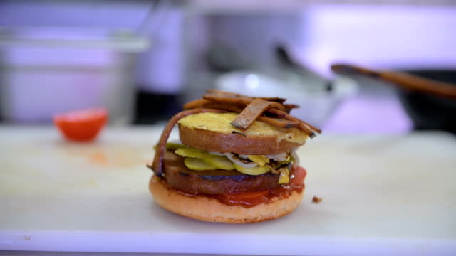 a vegan burger is displayed at the vegan seitan manufactory shop and diner l'herbivore by owner johannes theuerl on january 25 2018 in berlin germany... - alternative lifestyle stock videos & royalty-free footage