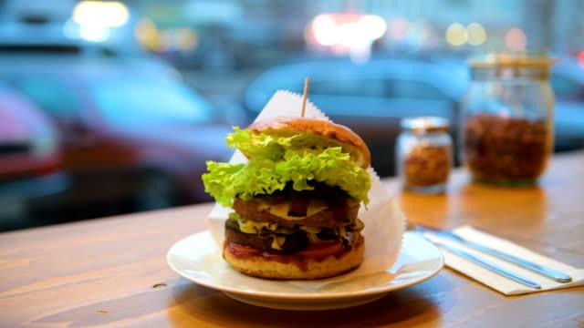 stockvideo's en b-roll-footage met a vegan burger is displayed at the vegan seitan manufactory shop and diner l'herbivore by owner johannes theuerl on january 25 2018 in berlin germany... - burger menselijke rol