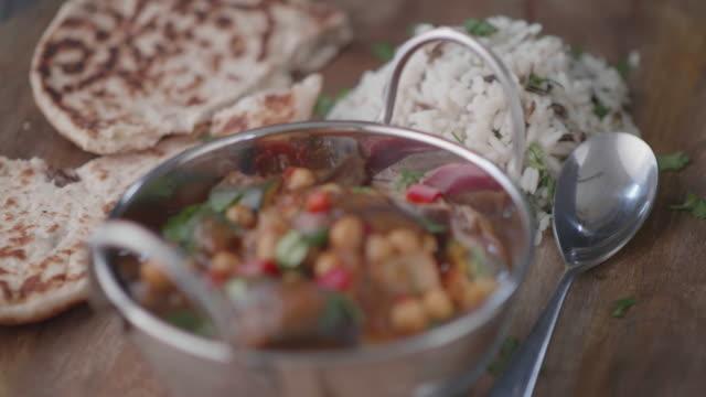木製のトレイに長い穀物の米とナンパンとビーガンひよこ豆、オーベルジンバルティ - カレー料理点の映像素材/bロール