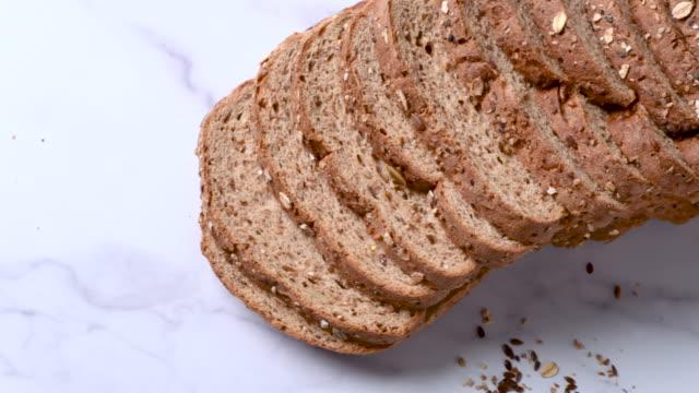 vidéos et rushes de vegan biologique 21 grains et graines de pain tranché d'en haut - quartier