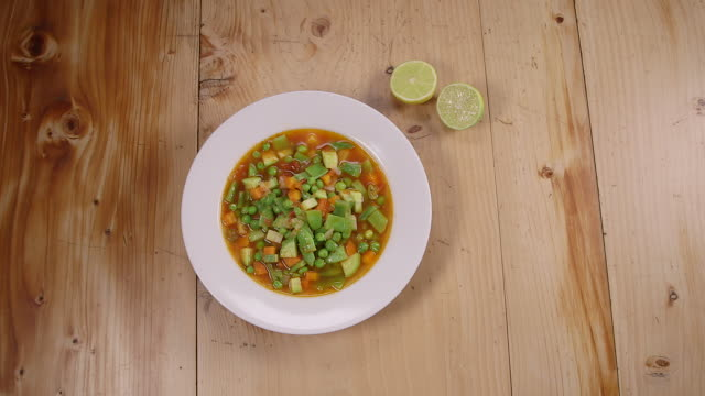 stockvideo's en b-roll-footage met vegetable soup. top view of a bowl of vegetable soup garniched with a sliced lemon. - sperzieboon