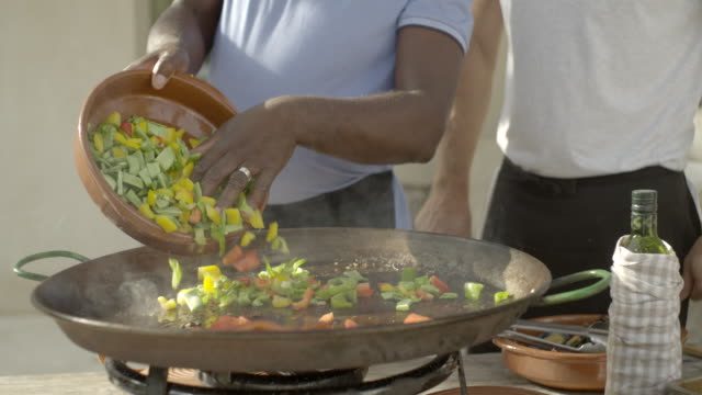 vegetables are poured into a paella pan - meal prepping stock videos & royalty-free footage
