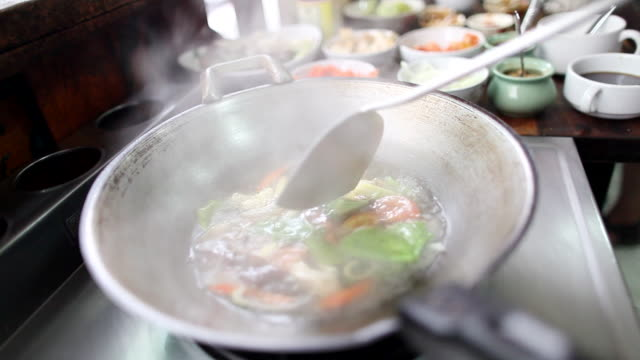 cu vegetables being cooked  in  wok making thom yum soup in / bangkok, bangkok, thailand - boiled stock videos and b-roll footage
