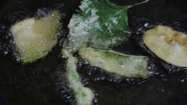 CU Vegetables being deep fried with batter for the preparation of Tempura / Tokyo, Tokyo-to, Japan