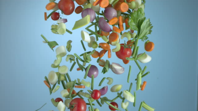 Vegetables fall against a blue background.