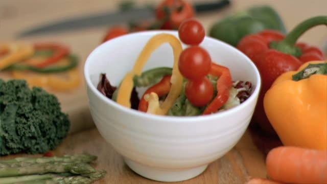 vegetables falling into bowl in super slow motion - オレンジピーマン点の映像素材/bロール