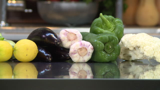 vegetables panleft on a cauliflower green bell peppers garlic aubergines lemons and zucchini placed on a kitchen counter - crucifers stock videos & royalty-free footage
