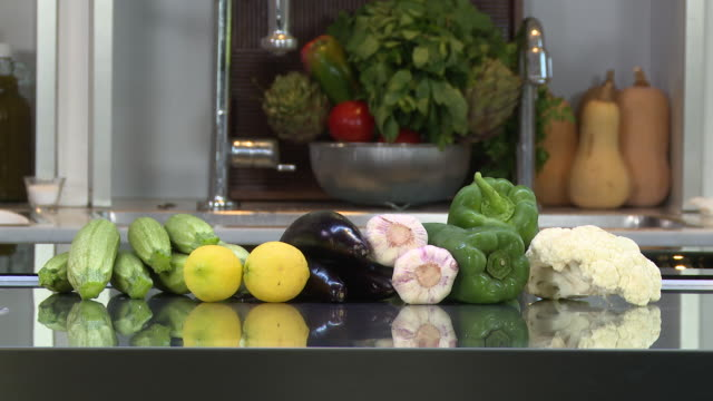 vegetables view of a cauliflower green bell peppers garlic aubergines lemons and zucchini placed on a kitchen counter - cauliflower stock videos & royalty-free footage