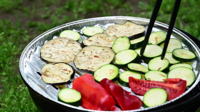 vegetarian barbecue with zucchini, red pepper and eggplant. someone moves it around with tweezers so they don't burn germany. - aluminium stock videos & royalty-free footage