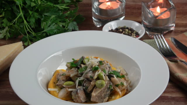 vídeos de stock e filmes b-roll de vegetarian tofu and mushroom stroganoff on a bed of yellow eggplant. - strogonoff
