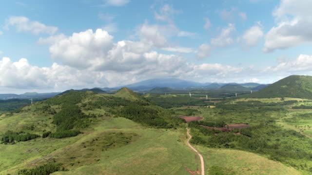 vegetation field and volcanic cones in jeju island - naturwunder stock-videos und b-roll-filmmaterial