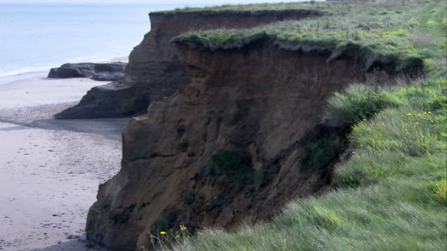 Vegetation lines the top of eroded cliffs along the North Sea. Available in HD.