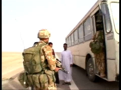 vehicle along road thru desert track soldiers out of helicopter soldiers checking coach at checkpoint as iraqi men standing looking on major chris... - channel 4 news stock videos and b-roll footage