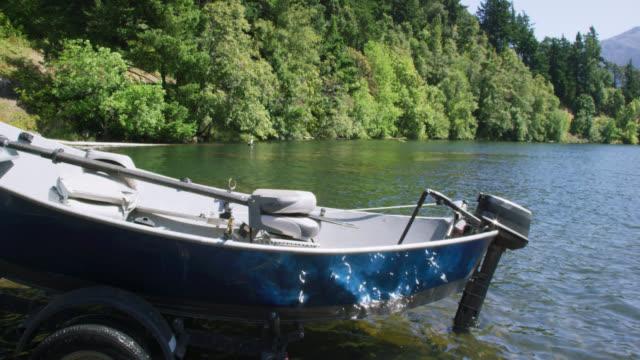 stockvideo's en b-roll-footage met een voertuig steunt een aanhangwagen en een kleine boot omhoog onderaan een helling van de boot en in de rivier van colombia in washington op een zonnige dag - aanhangwagen