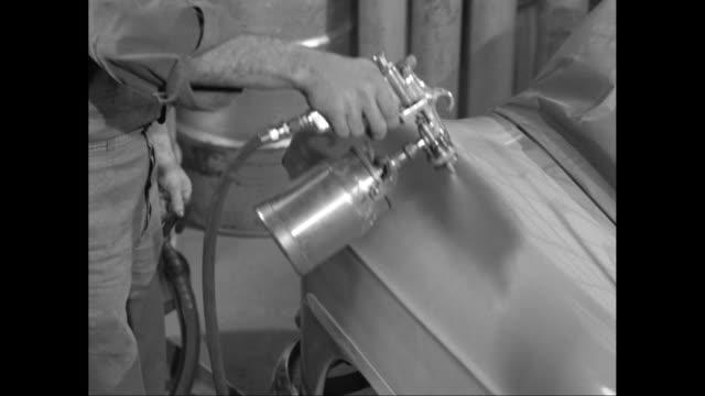 MS Vehicle bodywork repair technician holding paint dispenser, spraying car / United States