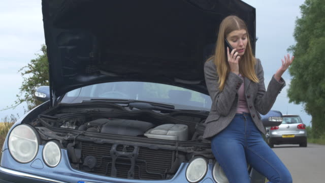 vidéos et rushes de vehicle breakdown.young woman at roadside. - panne de voiture