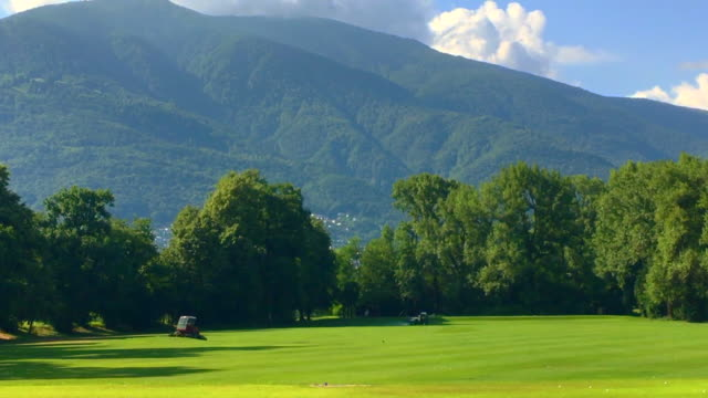 vehicle cutting the grass on golf driving range with mountain and trees in a sunny day in ascona, ticino, switzerland. - driving range stock videos & royalty-free footage