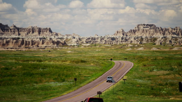vehicle drive in badlands national park sandstone buttes - south dakota stock-videos und b-roll-filmmaterial