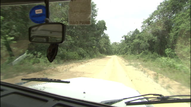 vídeos de stock, filmes e b-roll de a vehicle drives along a dirt road that passes through a forest in brazil. - estrada rural