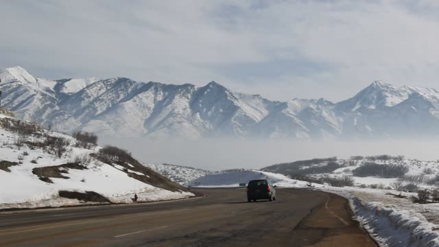 vídeos de stock, filmes e b-roll de a vehicle drives down little cottonwood canyon into a smogfilled valley caused by a winter temperature inversion in salt lake city utah us on... - cottonwood canyon