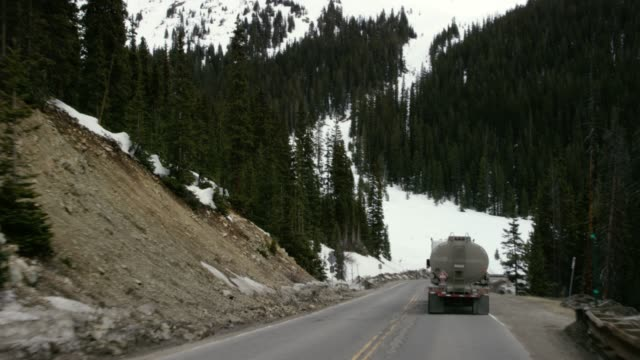 a vehicle drives down the winding road of loveland pass behind an oil tanker on the continental divide in the rocky mountains of colorado under an overcast sky in winter - road sign stock videos & royalty-free footage