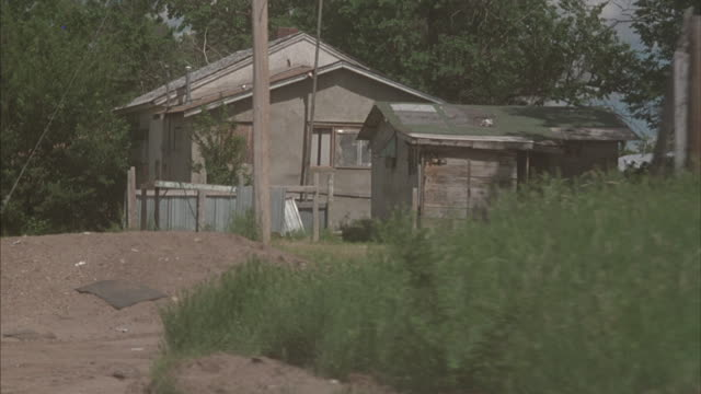 vídeos de stock e filmes b-roll de a vehicle drives through a poor rural neighborhood where two children play near a working-class house. - cultura tribal da américa do norte