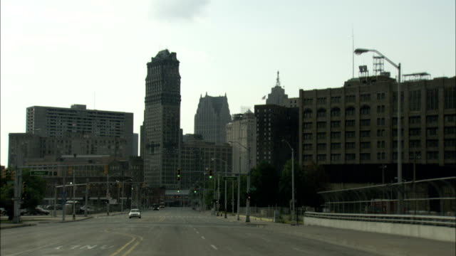 a vehicle drives towards the historical financial district of downtown detroit, michigan. available in hd. - michigan点の映像素材/bロール