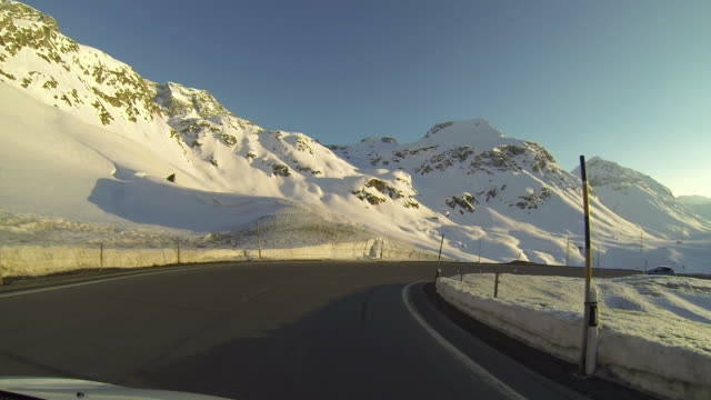 Vehicle POV driving on snowy mountain road at sunset