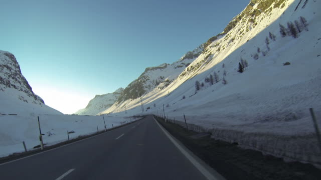 Vehicle POV driving on snowy mountain road