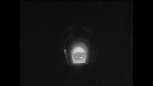 vídeos de stock, filmes e b-roll de a vehicle emerges from an unlighted tunnel. - túnel estrutura feita pelo homem