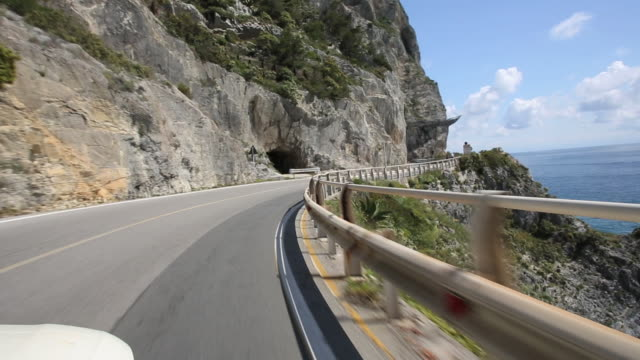POV of vehicle following coastal road with cliffs overhead