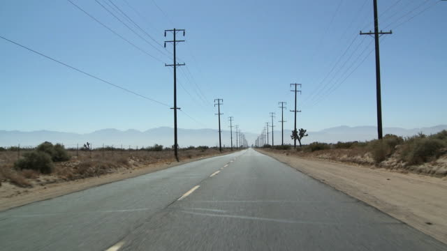 ws pov vehicle moving on desert highway, telephone poles / palmdale, california, usa    - telegraph pole stock videos and b-roll footage
