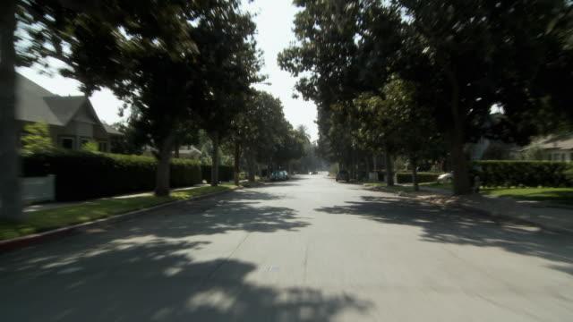 ws pov vehicle moving through shady leafy neighborhood / south pasadena, california, usa - 乗物後部から見た視点点の映像素材/bロール
