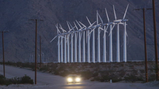 LS Vehicle on desert road with wind turbines in background / Palm Springs, California