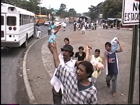 vídeos y material grabado en eventos de stock de vehicle passes buses and boys at a stop light selling cold water from plastic bags on the outskirts of managua, nicaragua in 1999. they say over and... - nicaragua