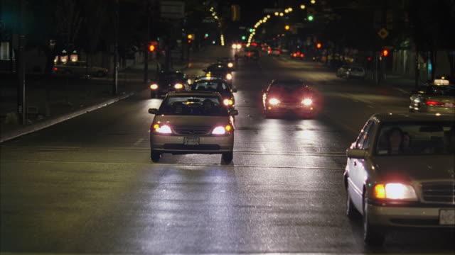 WS POV Vehicle passing through city street at night / Vancouver, British Columbia, Canada