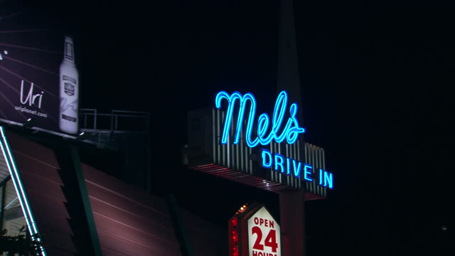 vehicle pov, ts past signage for mels drive in, sunset boulevard / hollywood, california, united states. - sunset boulevard stock-videos und b-roll-filmmaterial