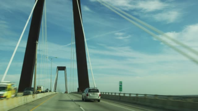 vehicle point of view of crossing hale boggs memorial bridge (suspension bridge) on interstate 310 over the mississippi river near baton rouge in southern louisiana under a partly cloudy sky - suspension bridge stock videos & royalty-free footage
