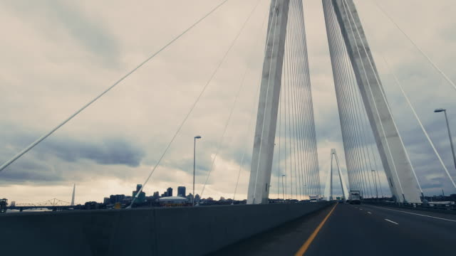 vehicle point of view of crossing the mississippi rivercrossing while traveling westbound on stan musial veterans memorial bridge (suspension bridge) on interstate 70 near st. louis, missouri and the missouri/illinois state border under a dramatic, stormy - river mississippi stock videos & royalty-free footage