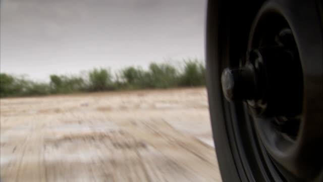 vídeos de stock, filmes e b-roll de a vehicle rolls through the little rann of kutch. available in hd. - estrada em terra batida