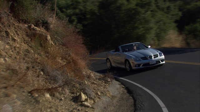vehicle pov, ts ms of silver mercedes-benz convertible car driving along forested mountain road / malibu canyon road, california, united states - mercedes benz stock videos and b-roll footage